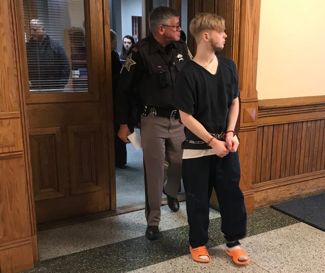 Seventeen-year-old John Vanderwielen is escorted from a Tippecanoe County courtroom Friday. Vanderwielen attended a hearing in which it was decided whether he would be able to have contact with his parents, who also are his alleged victims.