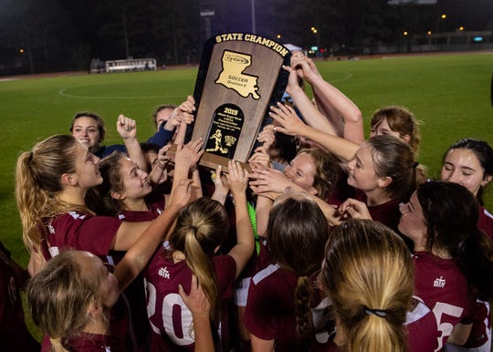 The St. Thomas More Lady Cougars celebrate after defeating Lakeshore to win the LHSAA Division II girls state soccer championship on Thursday, Feb. 21, 2019.