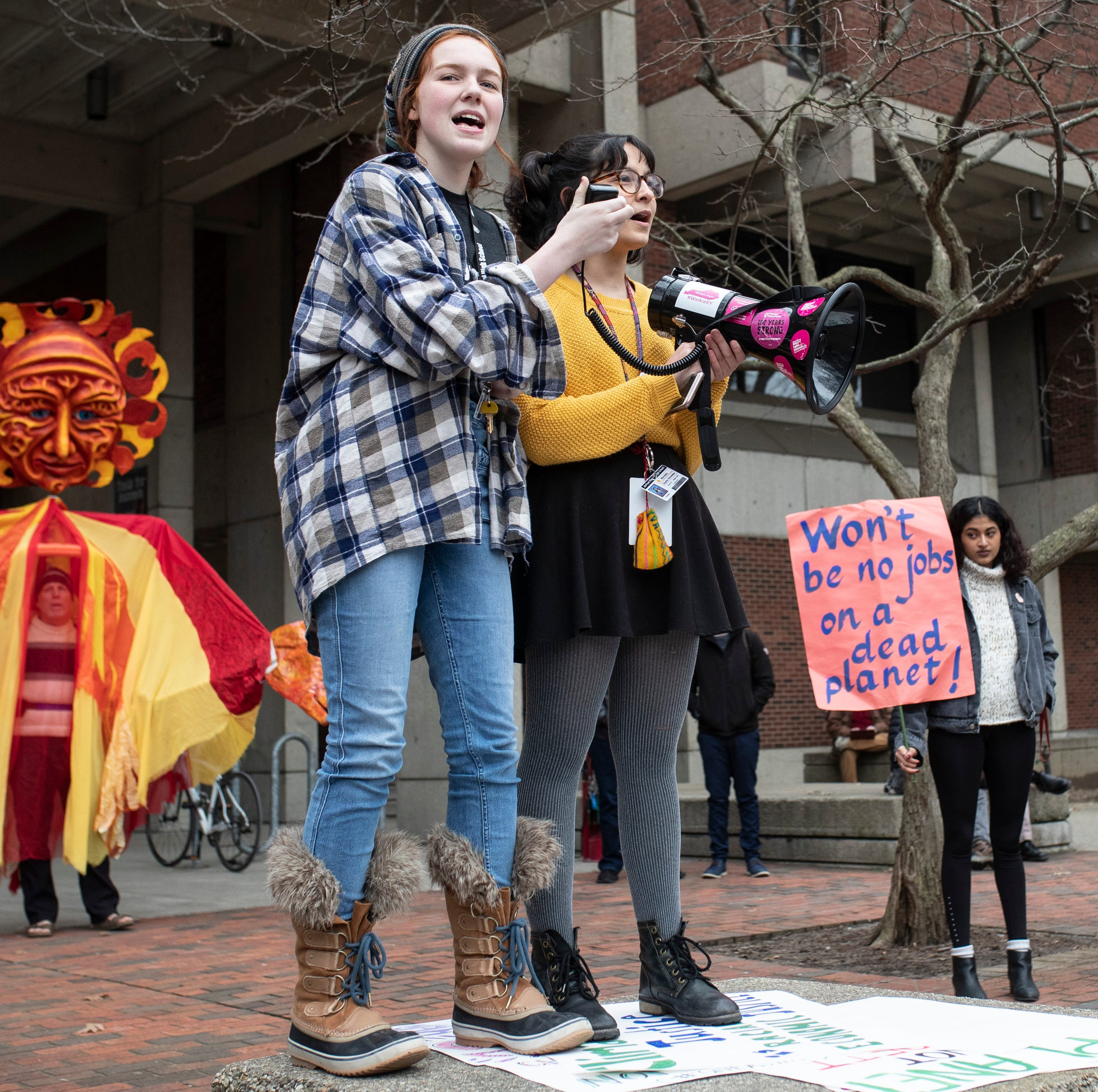 DuPont Manual students Marilyn Buente, left, and Mandala Gupta Verwiebe lead songs during a protest in support of the Green New Deal as well as climate and social justice on the U of L campus Friday. Feb. 22, 2019