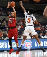 Louisville guard Asia Durr (25) shoots over Virginia guard Khyasia Caldwell (5) during the second half of an NCAA college basketball game Thursday, Feb. 21, 2019, in Charlottesville, Va.