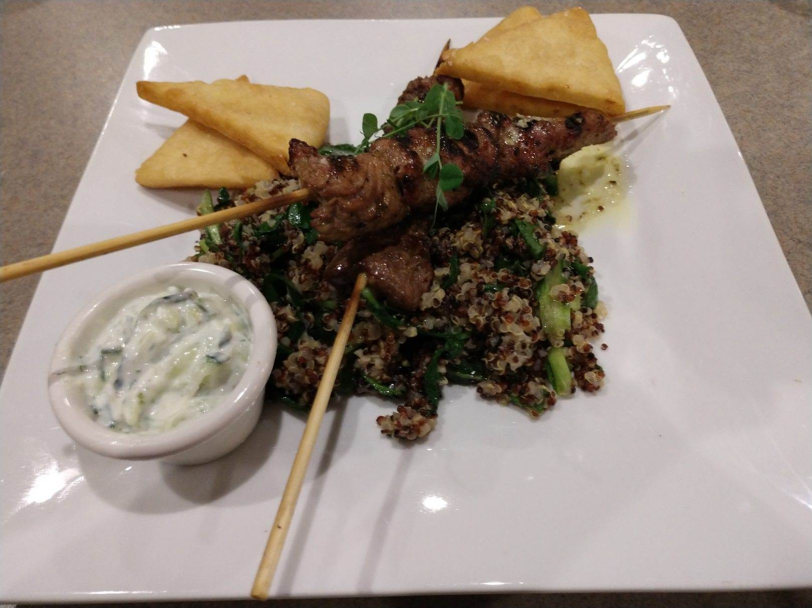 The souvlaki from Holla in Manitowoc is a Greek-style dish that features grilled lamb on skewers and served on a bed of quinoa, shallots and spinach along with pita chips and a house-made Tzatziki sauce.