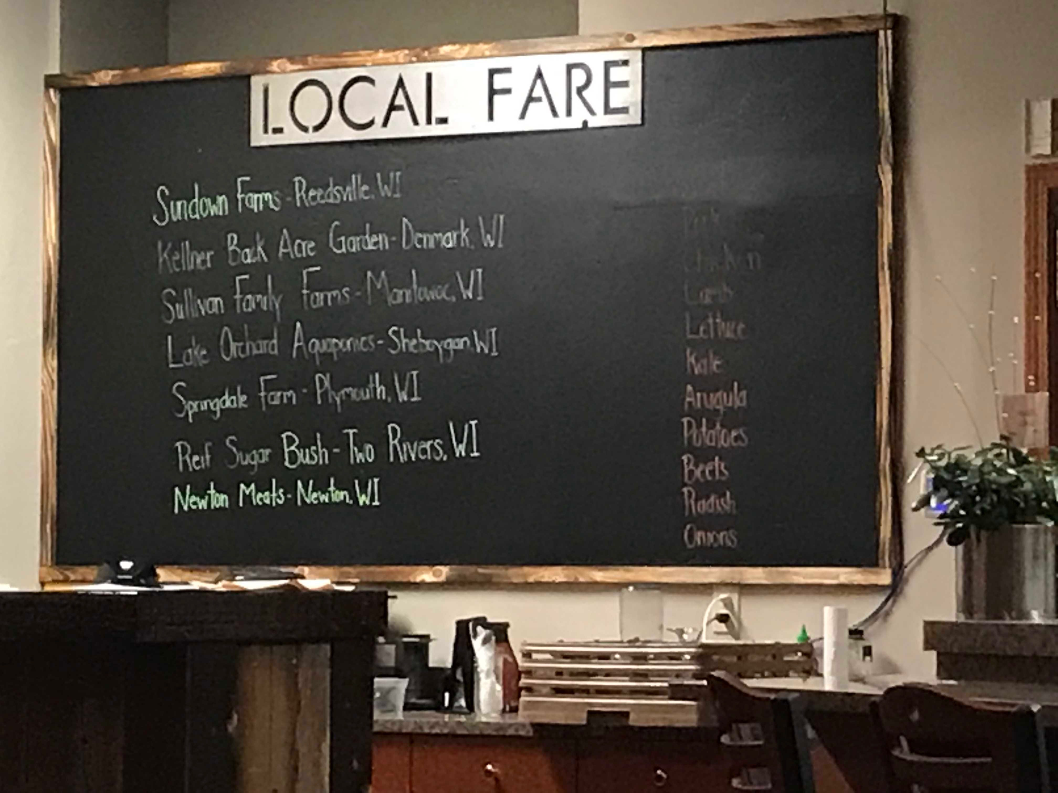 This board near the entrance to Holla, a new farm-to-table restaurant in Manitowoc, lists the farms and local businesses that supplied the food used for the night's dishes.