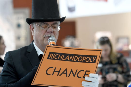 Neil Hamilton of Hamilton Insurance Group reads his Chance card while playing Richlandopoily at the Richland Mall.