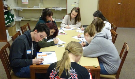 Students compose short stories from writing prompts during a writing  workshop at the Bucyrus Public Library on Friday.