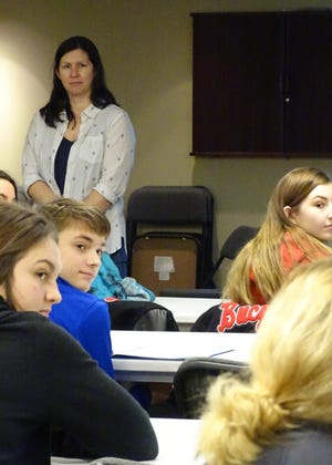 Author Mindy McGinnis and program participants listen while one student shares an idea during a writing  workshop at the Bucyrus Public Library on Friday.