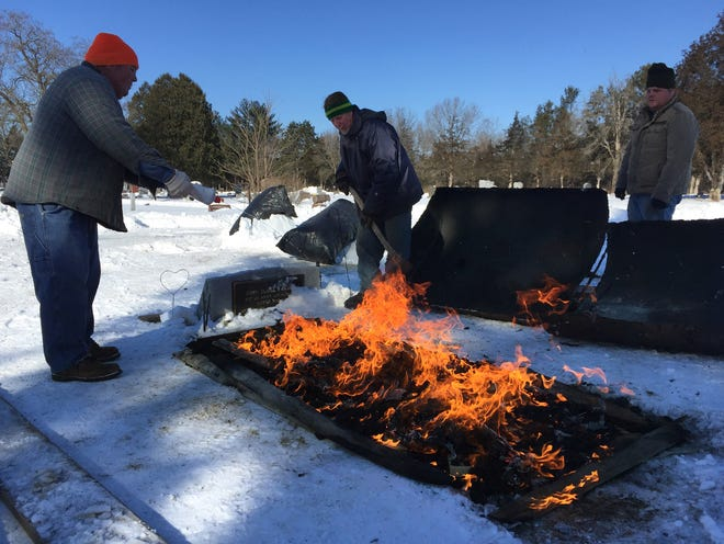Kris Bloedow (from left), Bill Jessen and Ben Bloedow light a bed of charcoal that will burn overnight and thaw the ground at a grave in Avoca Cemetery. They will dig the grave by hand the following day. Frost at the cemetery, located in Iowa County near the Wisconsin River, was about 20 inches deep.