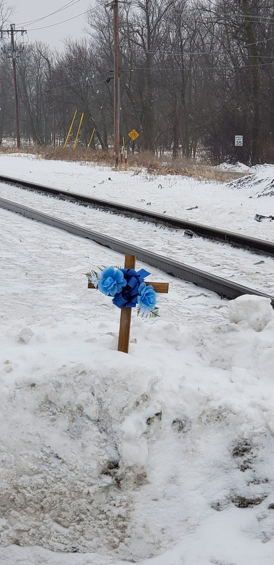 """On a snow pile, rests a wooden cross adorned with silk blue roses and ribbons in memory of Michael  """"Mike"""" J. Hayden, 70, of Brookfield who was killed in a train crash on Feb. 18."""