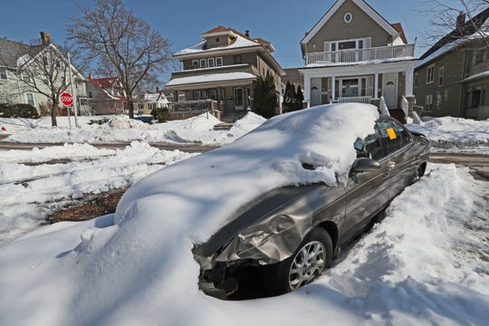 A parked car is buried in snow in the 2400 block of North Frederick Avenue in Milwaukee.