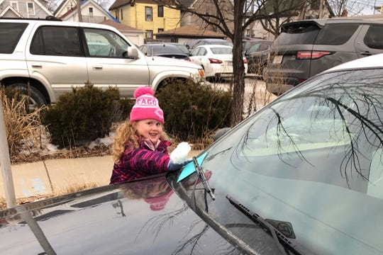 Five-year-old Allison Krueger places a card on a police officer's squad car. The Butler girl was inspired to start passing out Cards for Cops after Milwaukee Police Officer Matthew Rittner was killed in the line of duty Feb. 6.