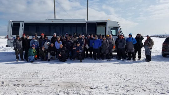 Military veterans and volunteers, including fishing guides, pose for a group photo at McKinley Marina in Milwaukee during the Feb. 18 ice fishing outing organized by Wisconsin Hero Outdoors.