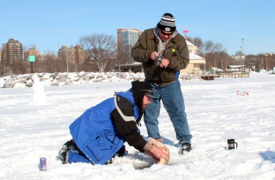 Fishing guide Andy Zollars of Milwaukee helps land a northern pike for U.S. Army veteran Thomas Old Coyote of Milwaukee on an ice fishing outing in McKinley Marina of Milwaukee organized by Wisconsin Hero Outdoors.
