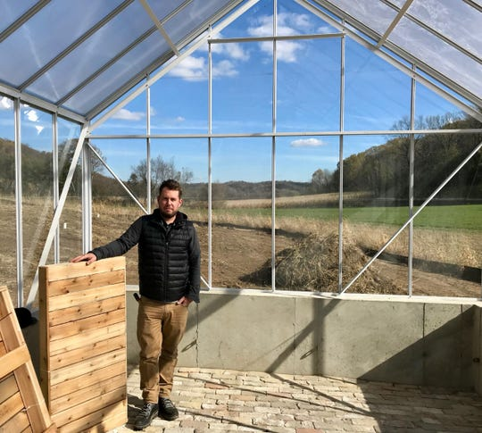 Jordan Hosking of Wisconsin Greenhouse Co. stands in one of the company's cottage-style greenhouses with a polycarbonate roof and a striking reclaimed brick floor using Milwaukee Creams and Chicago Pinks from The Brickyard Inc. in Milwaukee.
