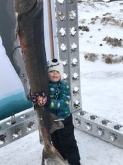 Theodore Harry, 3, hugs a 54-pound sturgeon caught during Fond du Lac's Sturgeon Spectacular, an annual winter festival on Lake Winnebago, where a reporter interviewed Wisconsin voters about next year's presidential election.