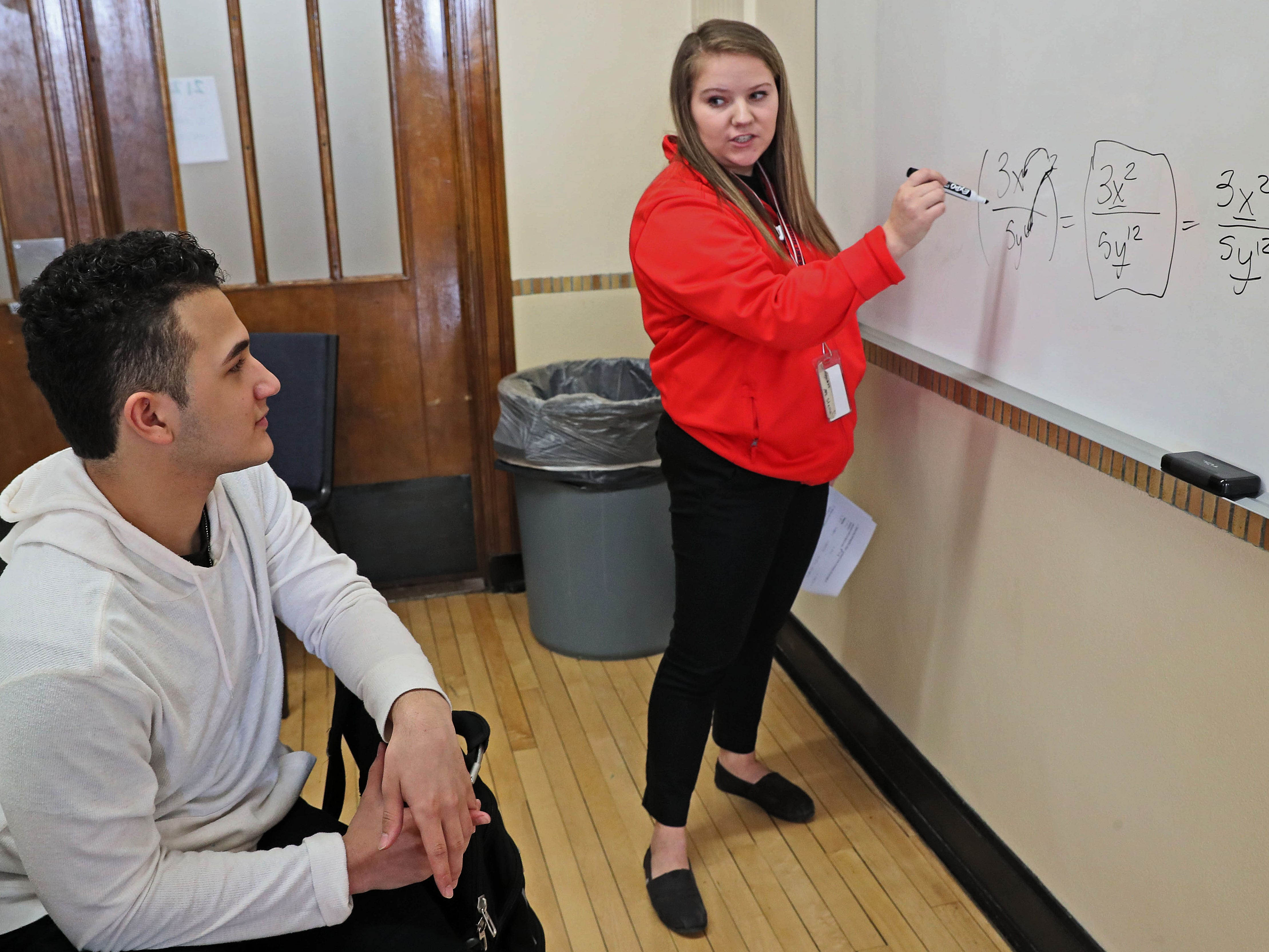 Student Daren Rosario (left), 15, works  on a math lesson presented by Stella Tomich, a City Year student success coach. City Year members work in MPS Casimir Pulaski High School in Milwaukee to teach, tutor and help students develop. They are working with ninth-graders, a key age group.