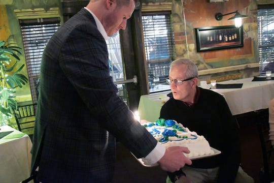 Craig Hayden holds a birthday cake honoring Mike J. Hayden, 70, of Brookfield. Mike died on Feb. 18 in a train crash.