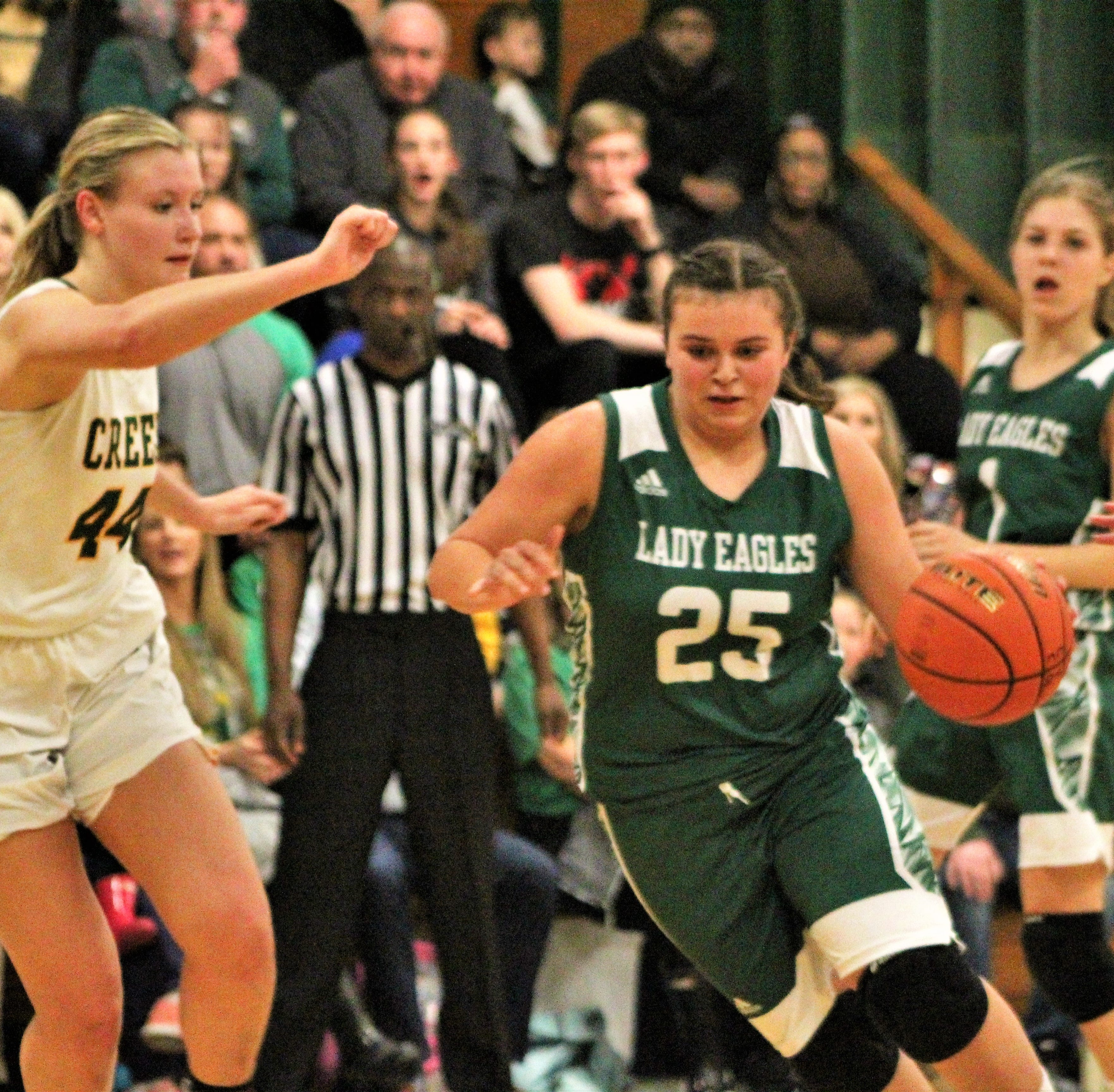 OCS's Madison Basco (25) dribbles the ball past Cedar Creek's Anna Larr Roberson (44) in OCS's 48-43 victory on the LHSAA Division IV quarterfinals at Cedar Creek's The Brickhouse on Thursday night.