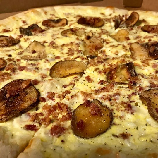 Eggs, cheese, potatoes and bacon, ham or sausage top the Walk of Shame pizza at Spinelli's. (You can get pizza until 5 a.m.)