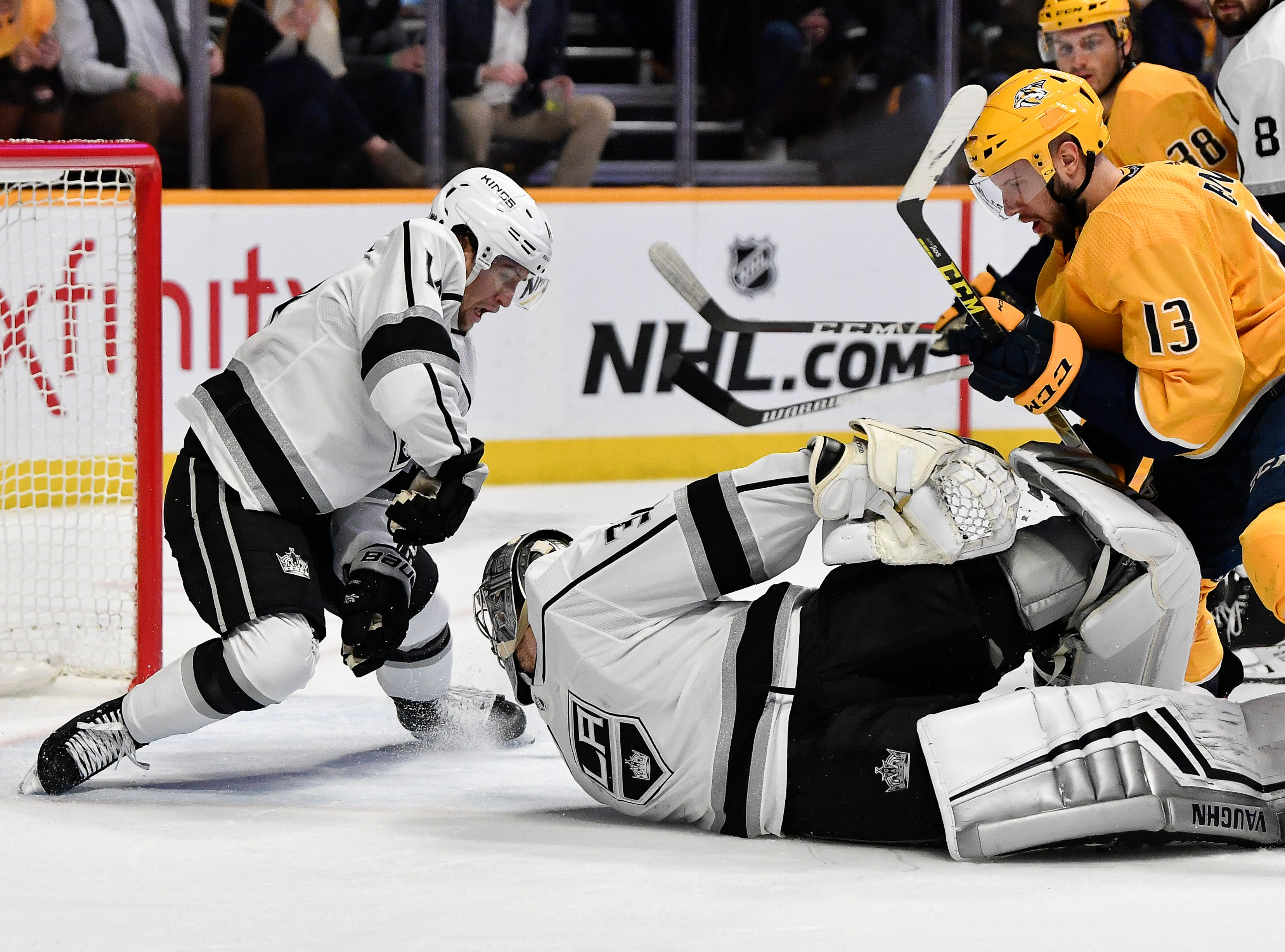 Kings goaltender Jonathan Quick (32) dives to keep a Predators shot on goal out of the net with help from left wing Brendan Leipsic (14) as Predators center Nick Bonino (13) attacks during the third period at Bridgestone Arena Thursday, Feb. 21, 2019 in Nashville, Tenn.