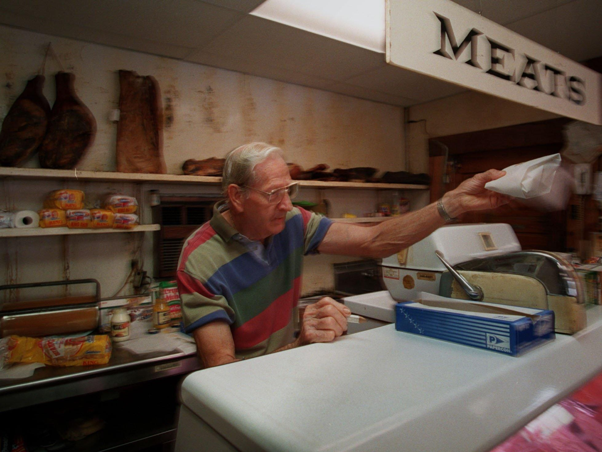 With aged and smoked meat on the shelf behind him, the owner of Terry's Market, Waymen Terry, handed a freshly made sandwich over the counter to a customer.