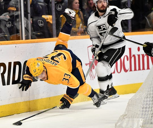 Predators right wing Viktor Arvidsson (33) is tripped up by a Kings defender during the first period at Bridgestone Arena Thursday, Feb. 21, 2019 in Nashville, Tenn.