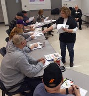 Lisa Scott, a work force trainer with Coshocton County Job and Family Services, hands out sample resumes at the AEP Plant in Conesville. The plant is set to shutdown in May 2020. AEP is working with local JFS on a series of job readiness to asses skills, develop soft skills and ascertain what new skills or education workers might need in obtaining new employment upon plant closure.