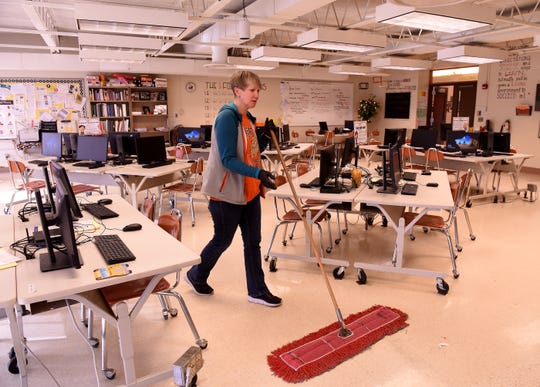 Ingrit Flowers, a second-shift custodian at Heath High School, cleans classrooms after most students have left for the day. Flowers has worked for the district for 12 years.