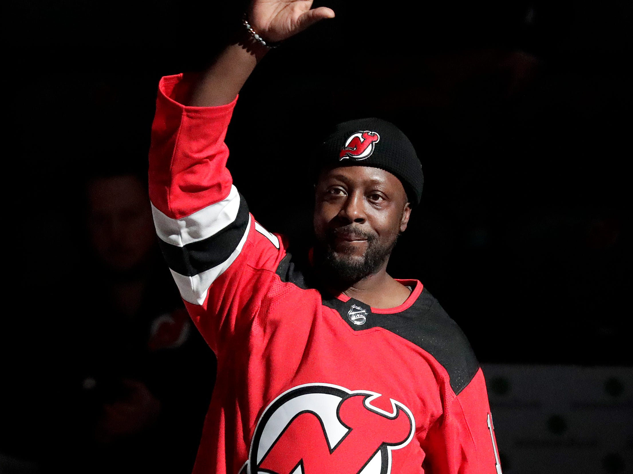 Rapper Wyclef Jean walks to center ice for the ceremonial puck drop prior to an NHL hockey game between the New Jersey Devils and the Ottawa Senators, Thursday, Feb. 21, 2019, in Newark, N.J.