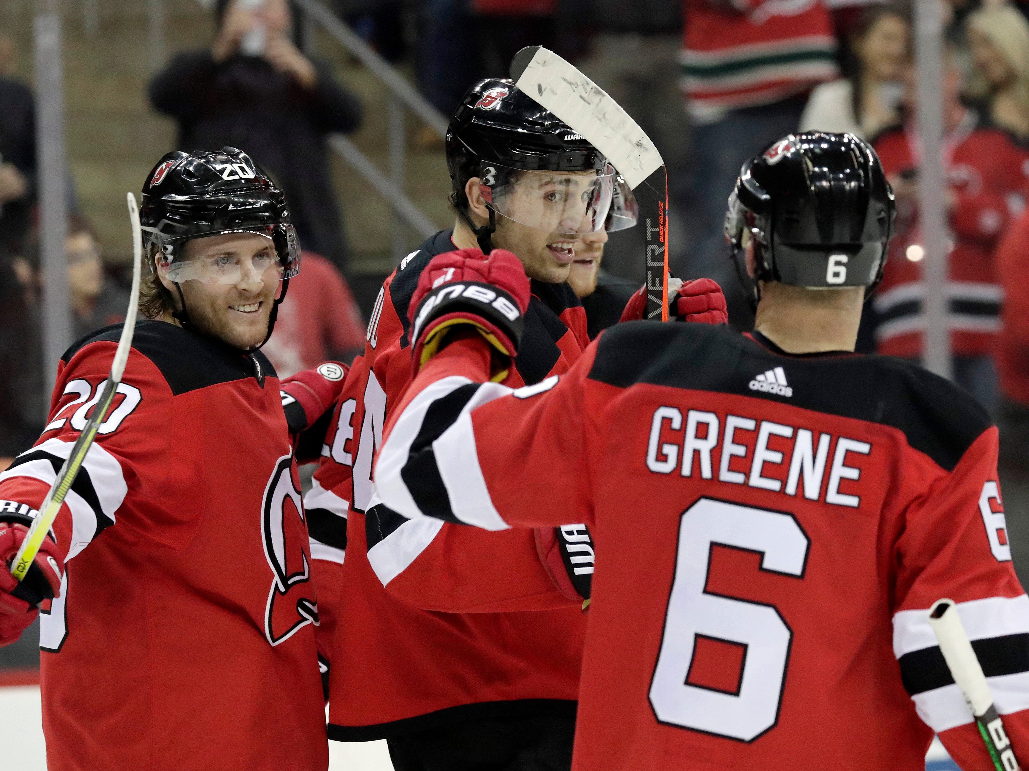 New Jersey Devils left wing Miles Wood, center, celebrates with teammates Blake Coleman (20) and Andy Greene (6) after scoring a goal against the Ottawa Senators during the second period of an NHL hockey game, Thursday, Feb. 21, 2019, in Newark, N.J.