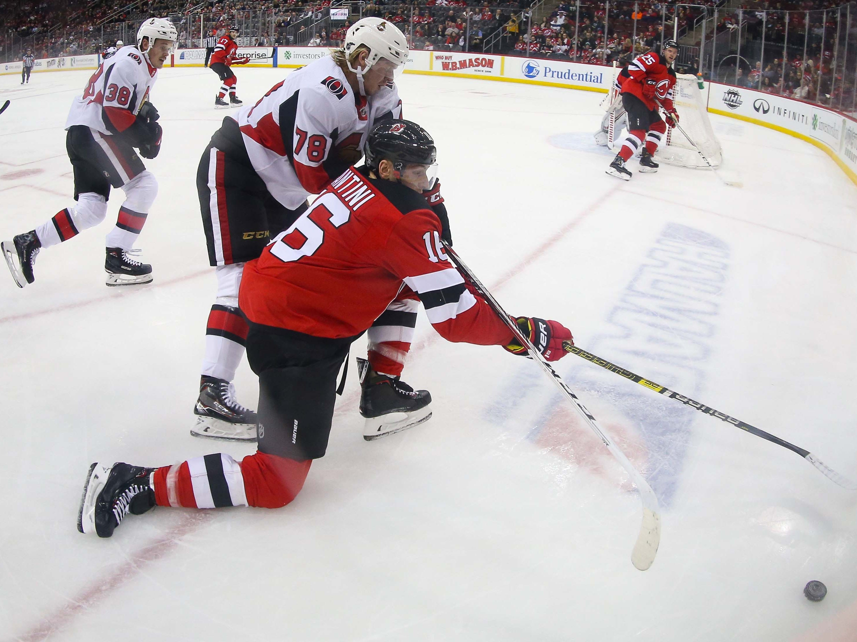 Feb 21, 2019; Newark, NJ, USA; New Jersey Devils defenseman Steven Santini (16) and Ottawa Senators center Filip Chlapik (78) battle for the puck during the first period at Prudential Center.