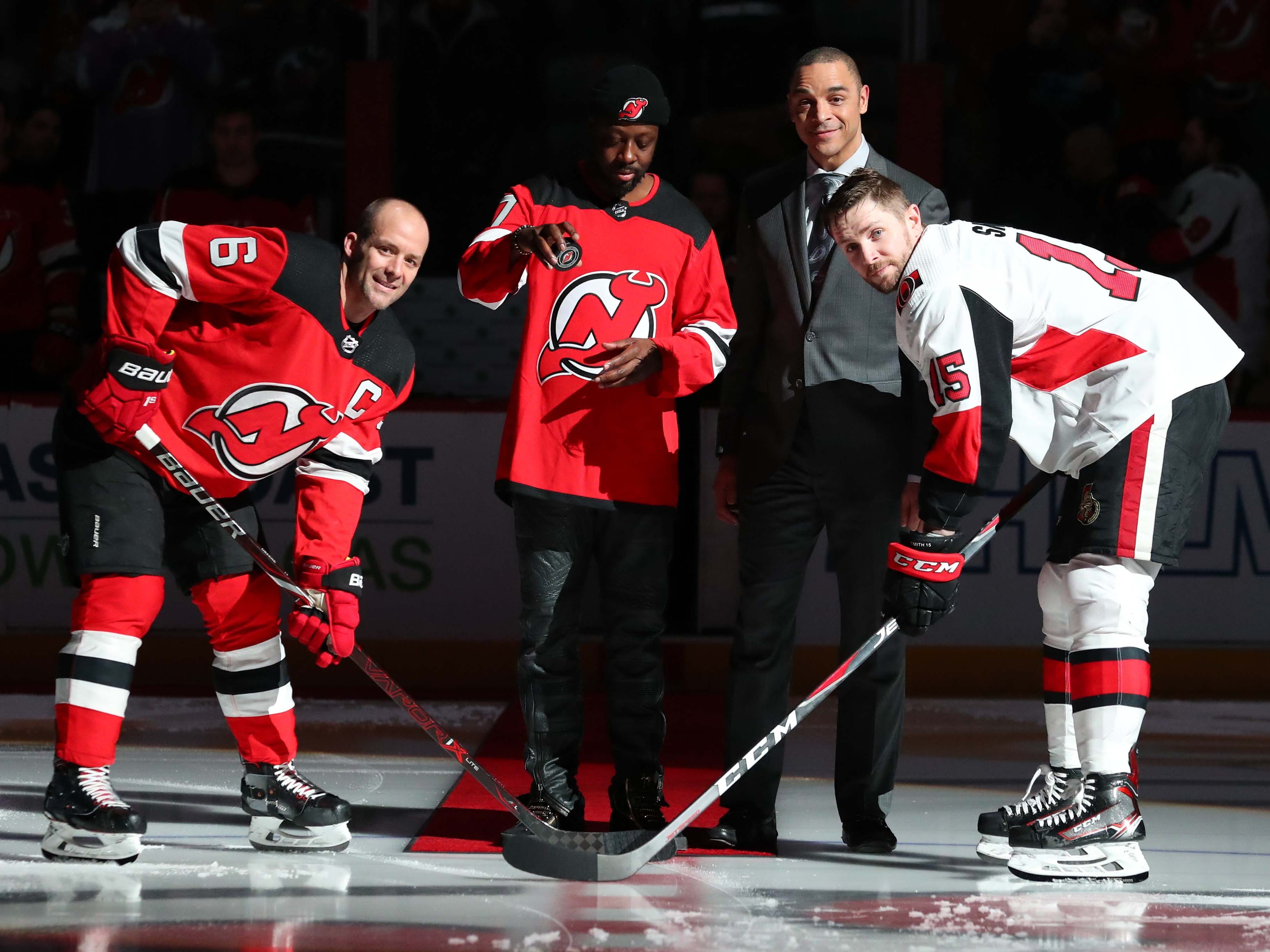 Feb 21, 2019; Newark, NJ, USA; Wyclef Jean, best known for performing in the band the Fugees, drops the first puck between New Jersey Devils defenseman Andy Greene (6) and Ottawa Senators left wing Zack Smith (15) at Prudential Center.