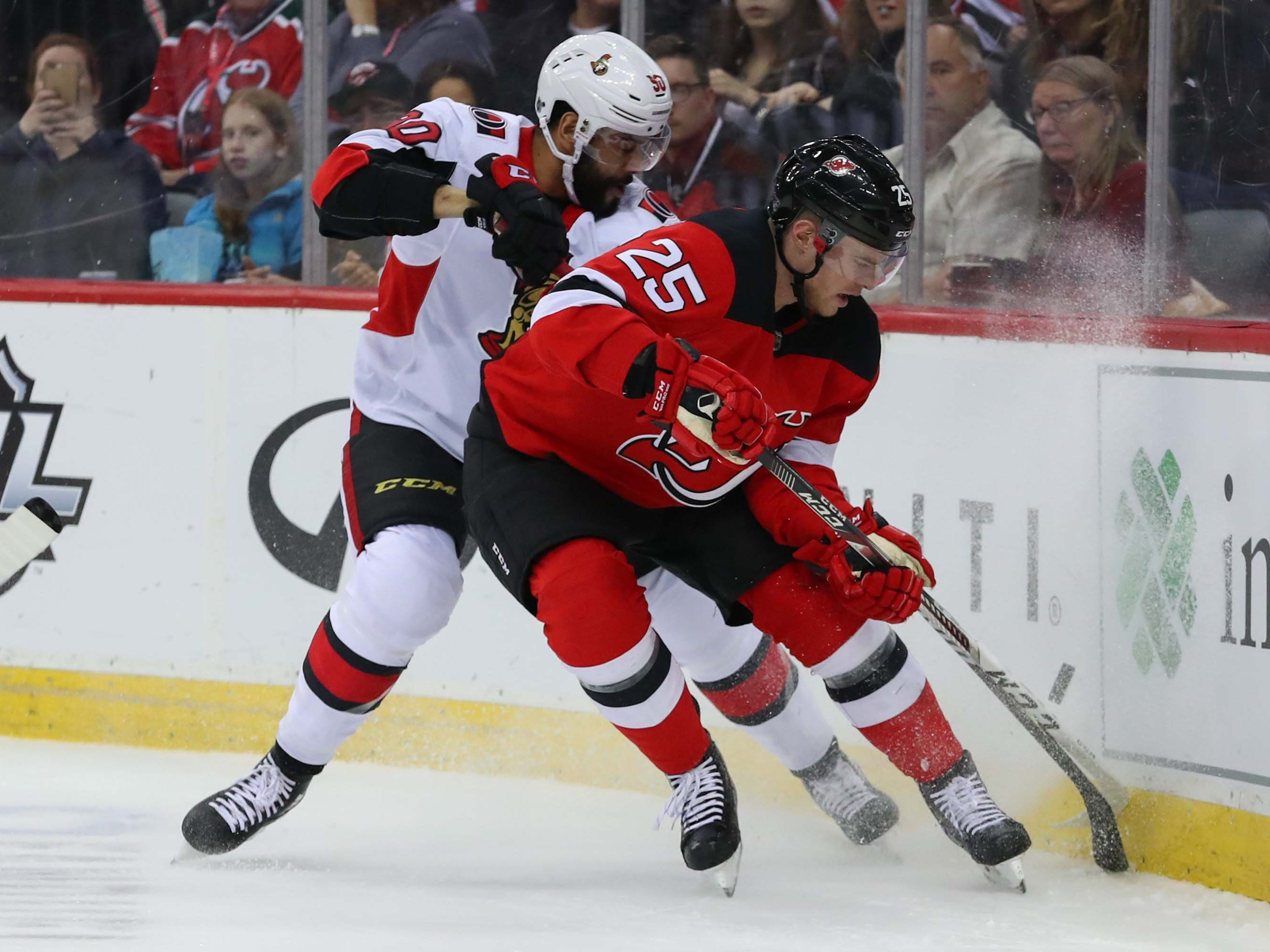 Feb 21, 2019; Newark, NJ, USA; New Jersey Devils defenseman Mirco Mueller (25) and Ottawa Senators right wing Darren Archibald (90) during the first period at Prudential Center.