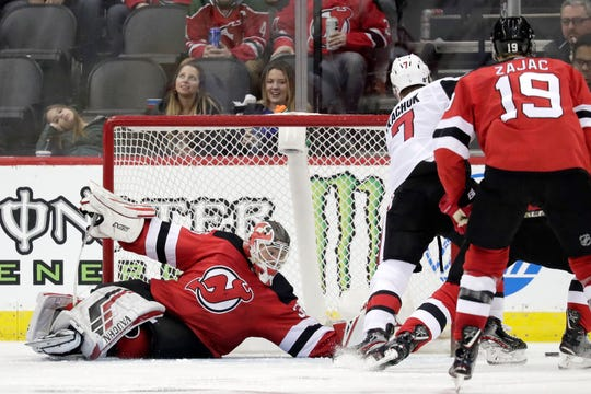 New Jersey Devils goaltender Cory Schneider, left, falls to the ice while reaching to defend against Ottawa Senators left wing Brady Tkachuk (7) during the second period of an NHL hockey game, Thursday, Feb. 21, 2019, in Newark, N.J.
