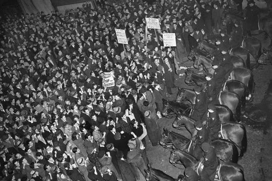"FILE -- This Feb. 20, 1939 file photo shows New York City's mounted police forming a line outside Madison Square Garden to hold in check a crowd that packed the streets where the German American Bund was holding a rally. he pro-Hitler rally that took place 80 years ago this week at New York's Madison Square Garden is the subject of a short documentary that's up for an Oscar this Sunday, Feb. 24, 2019. The film directed by Marshall Curry is called a ""A Night at the Garden."" (AP Photo/Murray Becker, File)"