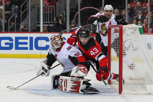 Feb 21, 2019; Newark, NJ, USA; New Jersey Devils left wing Brett Seney (43) crashes into Ottawa Senators goaltender Anders Nilsson (31) during the second period at Prudential Center.