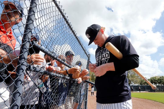 Feb 22, 2019; Tampa, FL, USA; New York Yankees left fielder Clint Frazier (77) signs autographs for fans as they holds balls though a fence while he works out at George M. Steinbrenner Field.