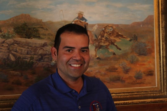 Edgar Torres, owner of Red Chimney Bar-B-Q stands in front of a painting in the restaurant in Carlsbad.