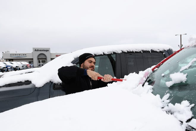 Advantage Dodge, Chrysler, Jeep and Fiat Lot Attendant Jesus Romero cleans snow off windshields of vehicles Friday morning in Farmington.