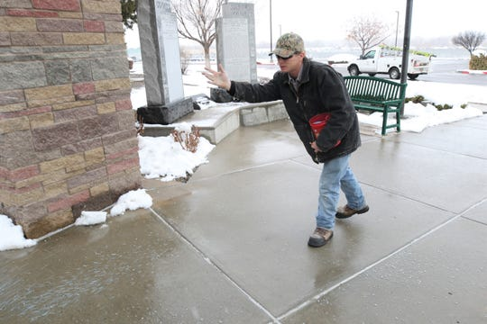 San Juan County maintenance employee Ian Clark throws snowmelt on the sidewalk outside the county's administration building in Aztec Friday morning.