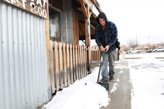 Serious Texas Bar-B-Q Pitmaster Logan Packer clears snow in the parking lot of the restaurant in Farmington Friday morning. A storm dropped upwards of 3.3 inches in Farmington.