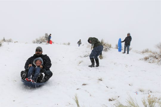 Richard Gutierrez and his son Emilliand Gutierrez sled down a hill south of Mesa Verde Elementary School along College Boulevard Friday morning.