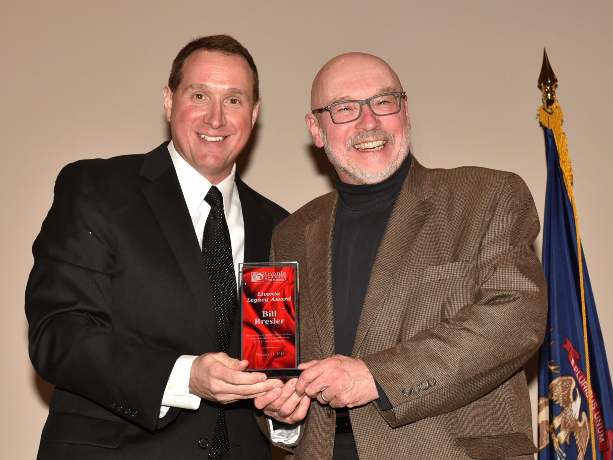 Dan West, left, congratulates recently-retired Observer and Eccentric photographer Bill Bresler with the Livonia Legacy Award on Feb. 21. Bresler covered the city of Livonia, and other local communities, for 40 years before retiring earlier this month.