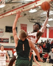 Canton's Sigmon Vinson tries to nail a fade-away shot near the hoop as he's guarded by Howell's Jake Sargeant.