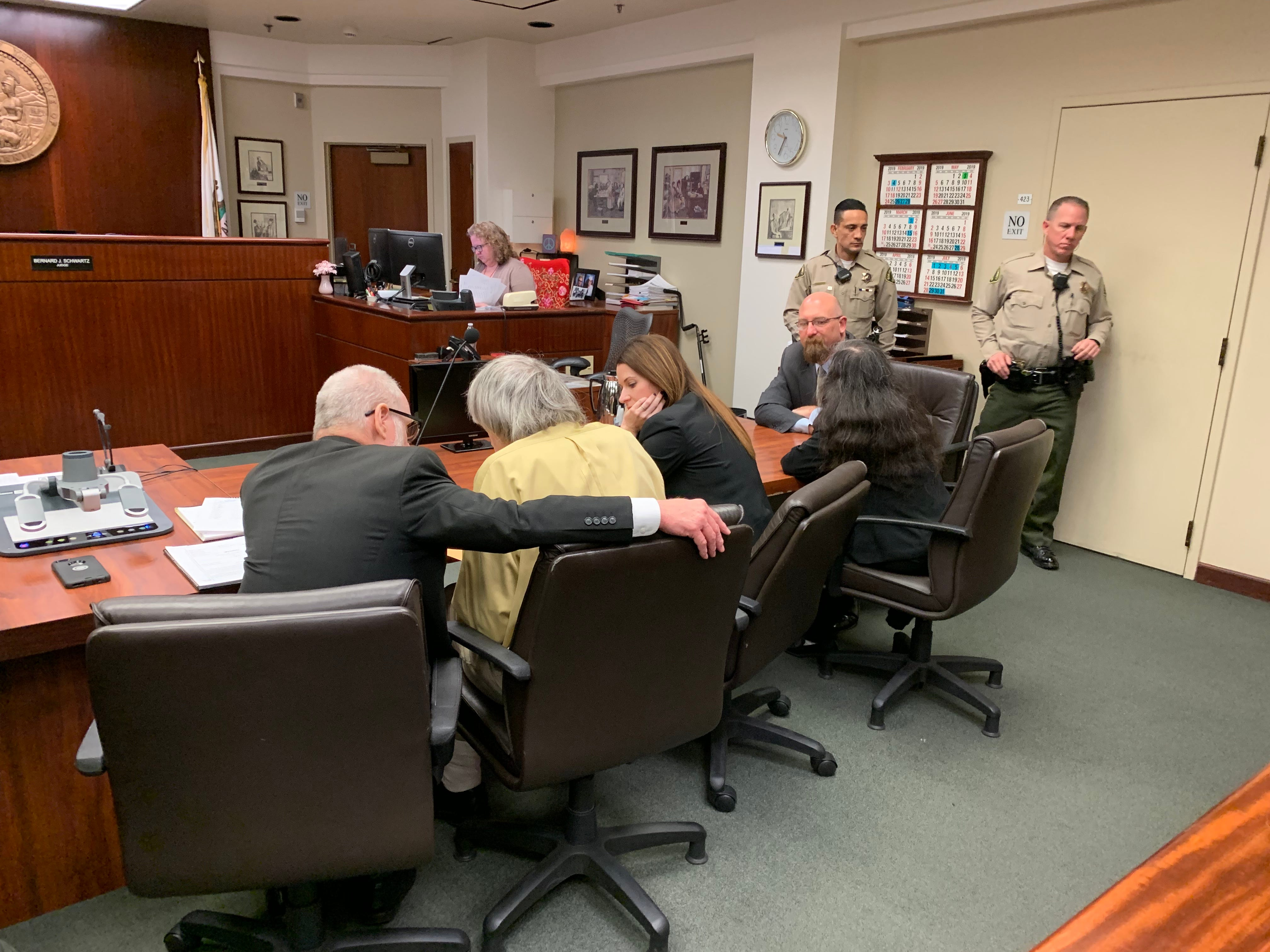 David Turpin, left wearing yellow shirt, confers with counsel after pleading guilty on several counts of torture and abuse on Feb. 22, 2019 in Riverside.