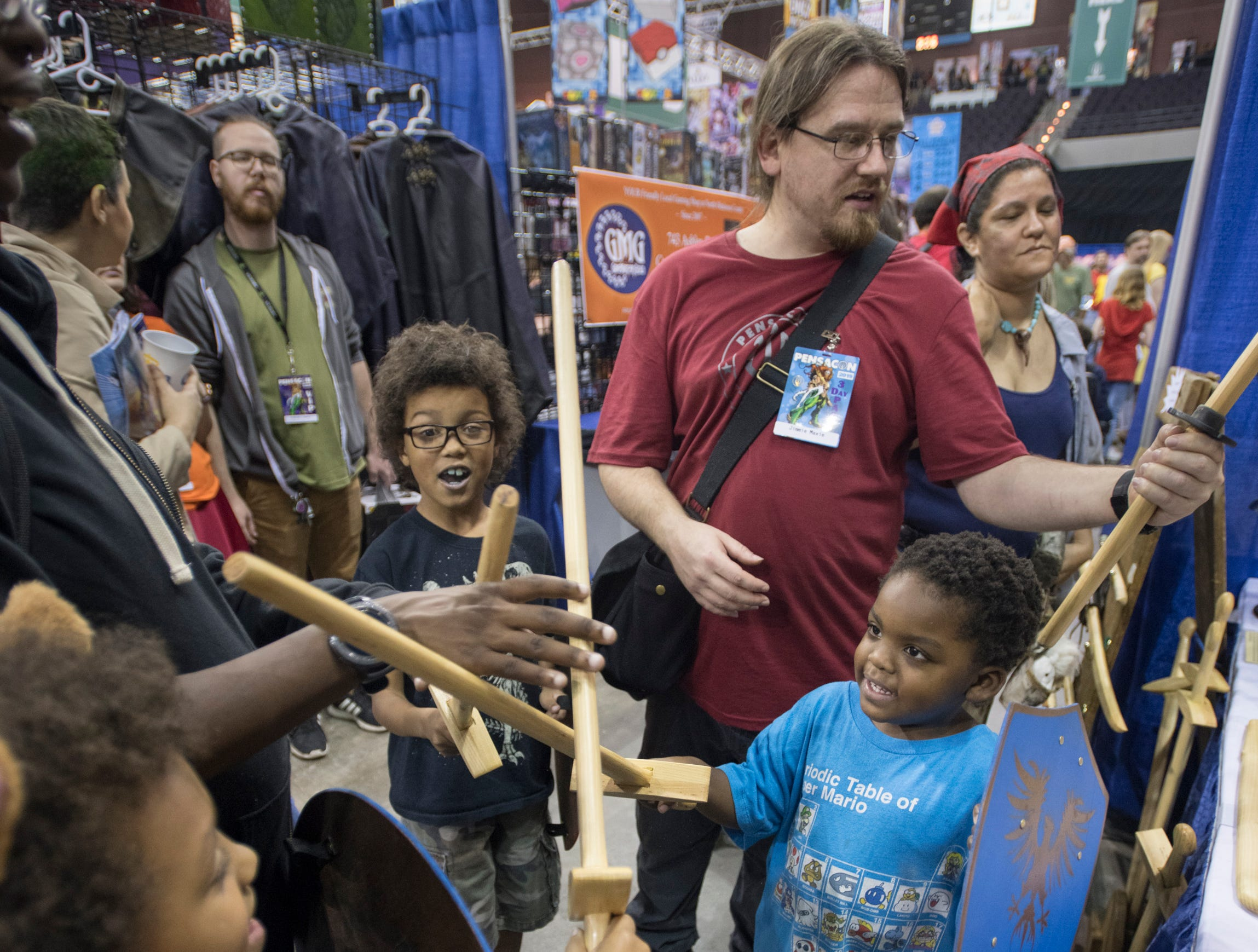 Brothers Geordi, 7, from left, Jimmie, 8, and Vash Maxie, 4, of De Funiak Springs, try out their new wooden swords during Pensacon at the Pensacola Bay Center on Friday, February 22, 2019.