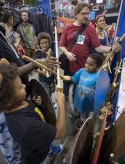 From left, brothers Geordi, 7,  Jimmie, 8, and Vash Maxie, 4, of DeFuniak Springs, try out their new wooden swords Friday during Pensacon at the Pensacola Bay Center.