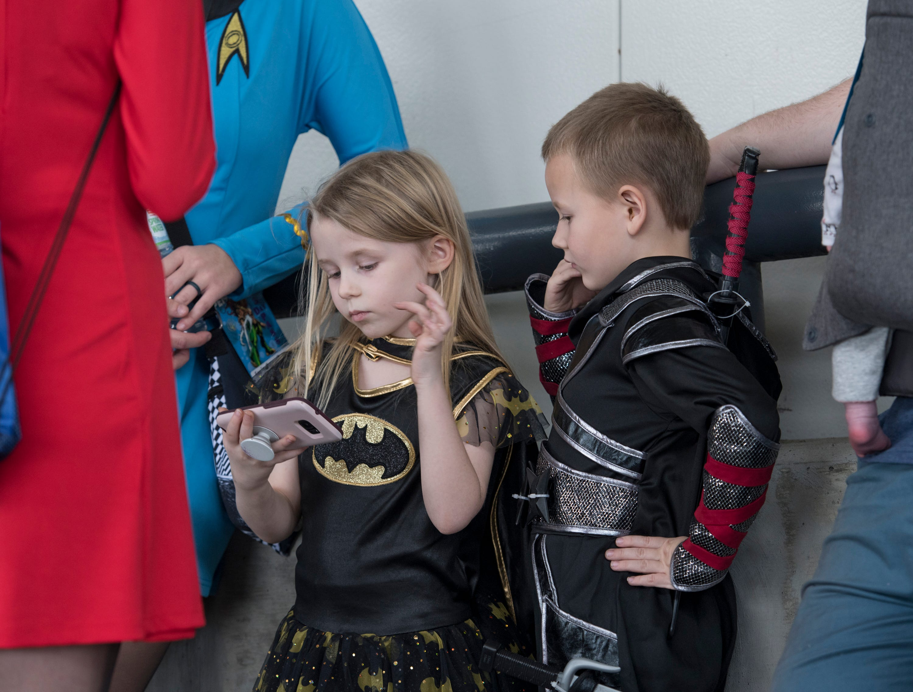Emma Jester, 5, and her brother William, 7, of Mobile, Alabama, kill time while waiting to enter Pensacon by playing with a cell phone at the Pensacola Bay Center on Friday, February 22, 2019.