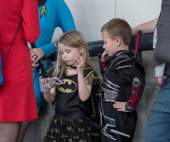 Emma Jester, 5, and her brother William, 7, of Mobile, Alabama, kill time Friday while waiting to enter Pensacon by playing with a cellphone at the Pensacola Bay Center.