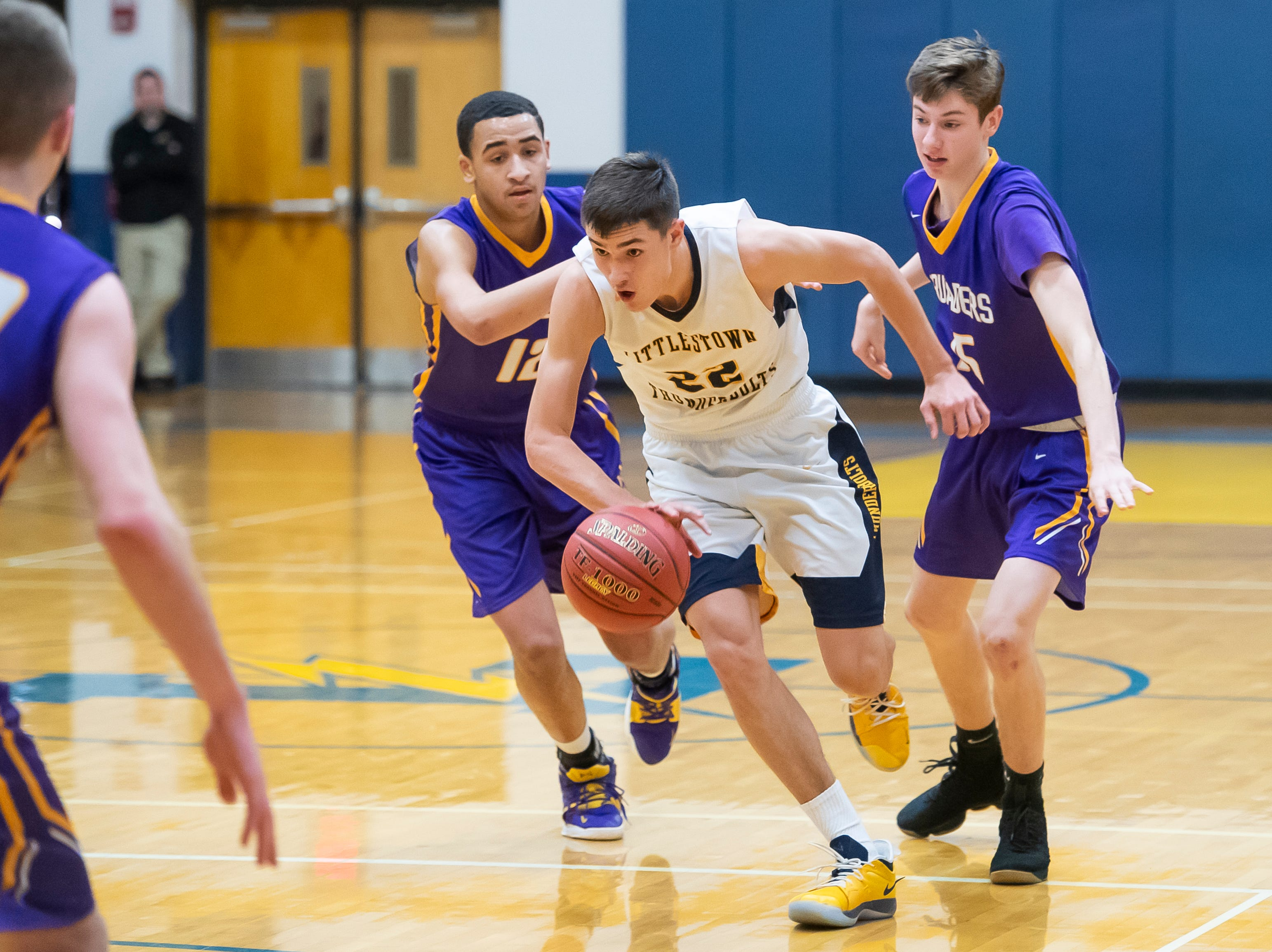 Littlestown's Logan Collins dribbles through Lancaster Catholic's Dwayne Caine (12) and Ross Conway (15) in the quarterfinals of the District 3 4-A playoffs Thursday, February 21, 2019. The Bolts fell 60-51.