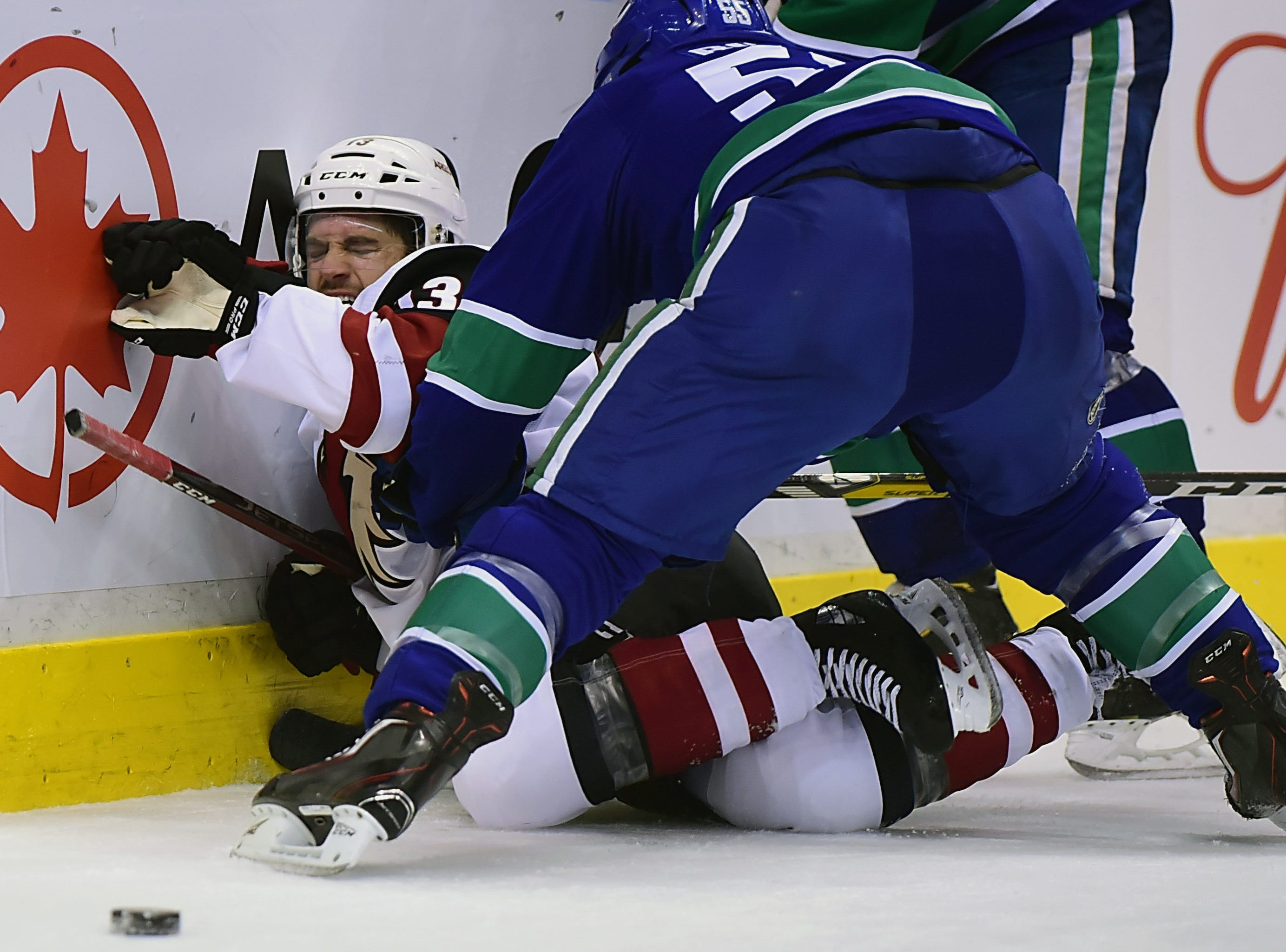 Feb 21, 2019; Vancouver, British Columbia, CAN; Vancouver Canucks defenseman Alex Biega (55) checks Arizona Coyotes forward Vinnie Hinostroza (13) during the second period at Rogers Arena. Mandatory Credit: Anne-Marie Sorvin-USA TODAY Sports