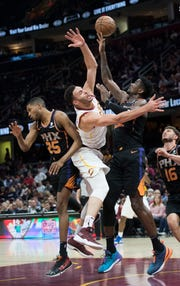 Feb 21, 2019; Cleveland, OH, USA; Phoenix Suns forward Mikal Bridges (25) and center Deandre Ayton (right) and Cleveland Cavaliers forward Larry Nance Jr. (middle) battle for a rebound during the second half at Quicken Loans Arena. Mandatory Credit: Ken Blaze-USA TODAY Sports
